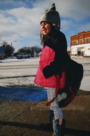 Girl standing on street in city during winter