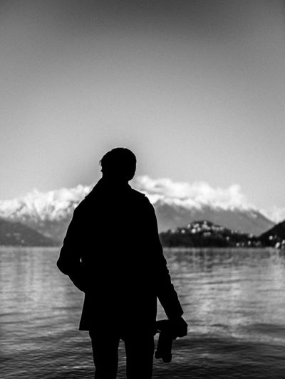 Rear view of silhouette man standing on pier over lake against sky