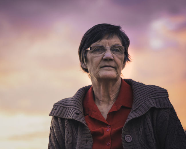 A low angle portrait of an elderly woman at sunset. Adult Casual Clothing Clothing Contemplation Eyeglasses  Focus On Foreground Front View Glasses Headshot Leisure Activity Lifestyles Looking At Camera One Person Portrait Real People Senior Adult Sky Sunset Waist Up Warm Clothing