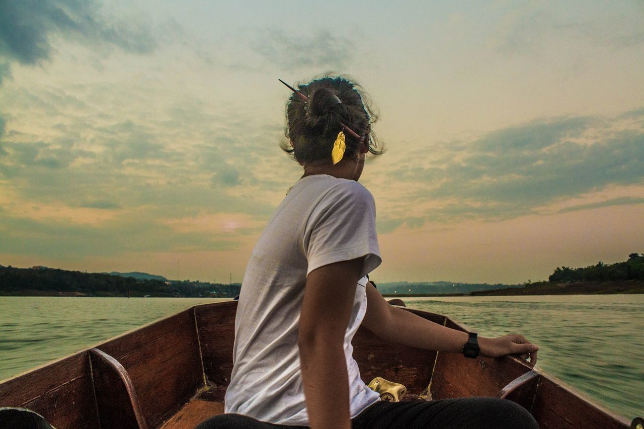 water, one person, nautical vessel, lake, transportation, real people, mode of transport, leisure activity, nature, sky, sitting, outdoors, scenics, cloud - sky, beauty in nature, day, vacations, tranquil scene, side view, tranquility, lifestyles, sunset, sailing, young adult, tree, people
