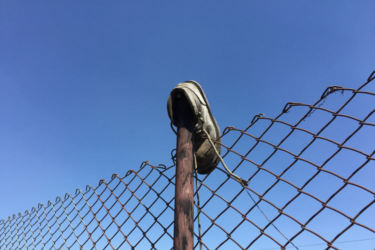 Low angle view of barbed wire fence against clear blue sky