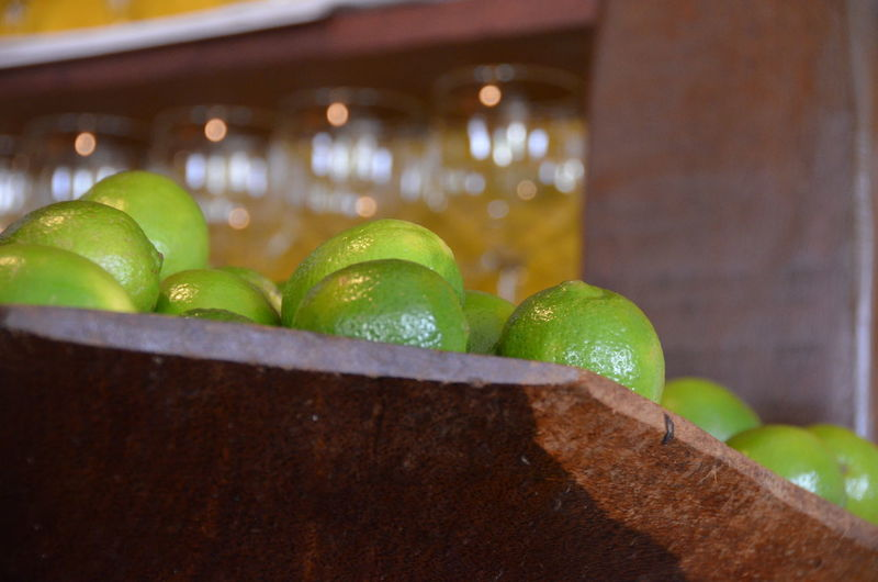 Close-Up Of Limes In Wooden Container At Bar