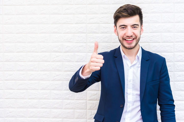 Portrait of confident man gesturing thumbs up while standing against wall