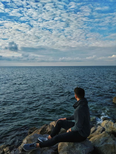 Sea side Man Blue Sea Ocean Slovenia Koper Seaside Beach Rocks Sky person Young Adult Youth Photography Autumn Water Water Sea Sitting Beach Relaxation Rear View Fishing Looking At View Sky