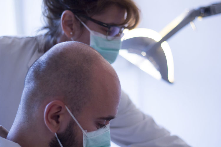 Close-up of doctors wearing surgical masks in hospital