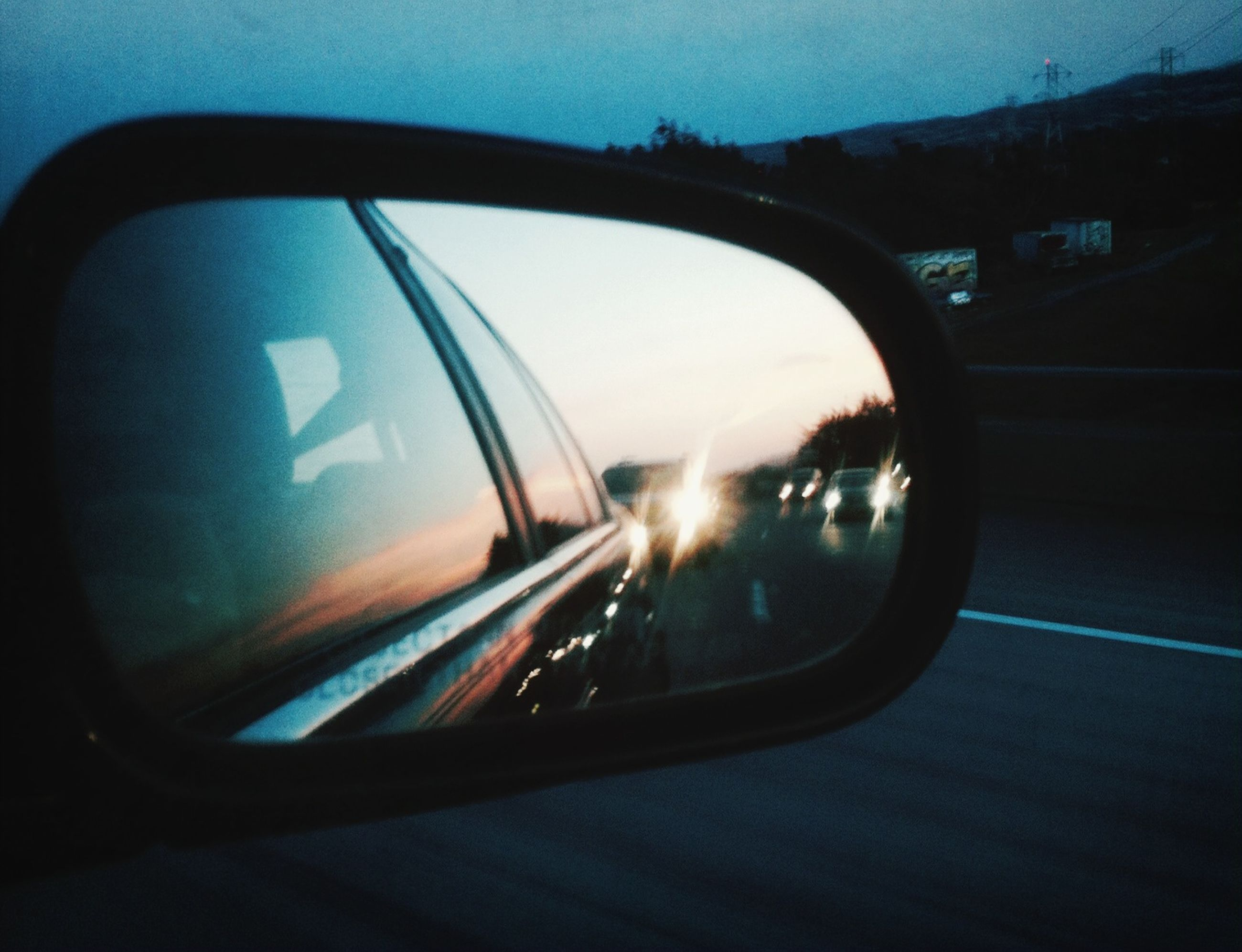 transportation, mode of transport, car, land vehicle, side-view mirror, glass - material, reflection, transparent, vehicle interior, window, car interior, road, sky, travel, on the move, street, sunset, windshield, part of, headlight