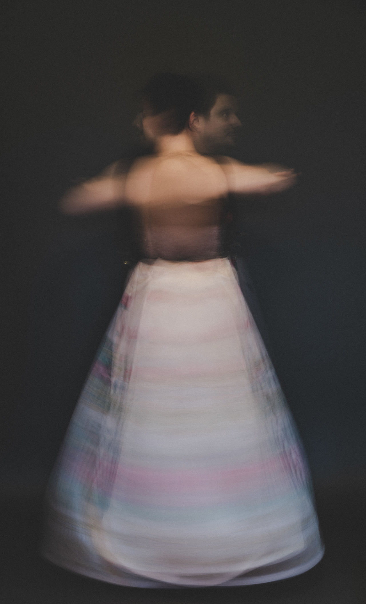 Blurred motion of woman spinning against black background
