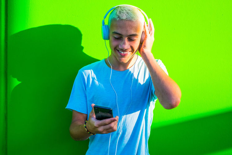 Smiling boy listening music while standing against green wall