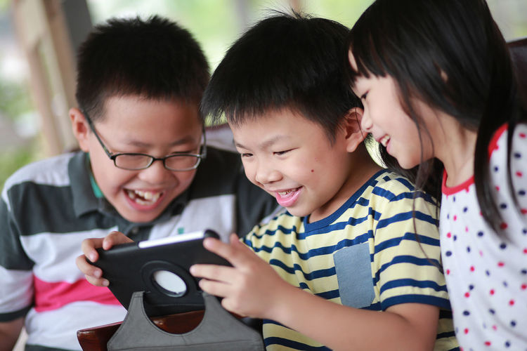 Asian kids using portable information device Asian  Boys Cheerful Child Childhood Cute Digital Native Education Elementary Age Elementary Student Enjoying Family Girls People Photography Themes Portable Information Device Smiling Student Tablet Technology Togetherness Mobile Conversations