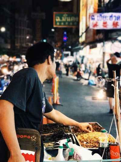 Man preparing food on street in city at night