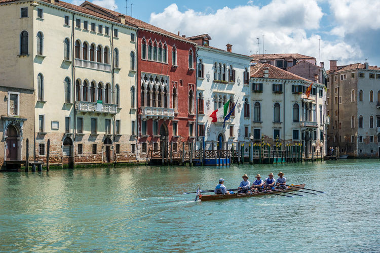People rowing boat in grand canal against buildings