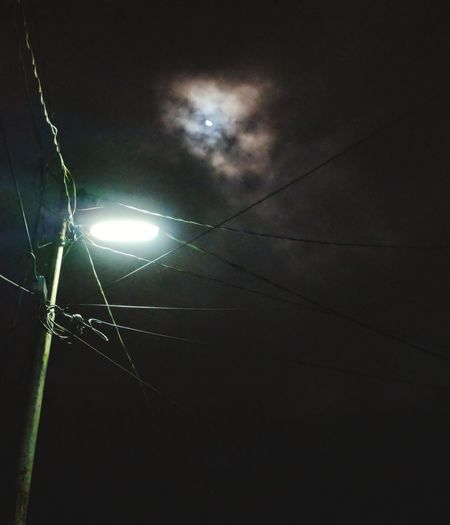 Low angle view of illuminated electricity pylon against sky at night