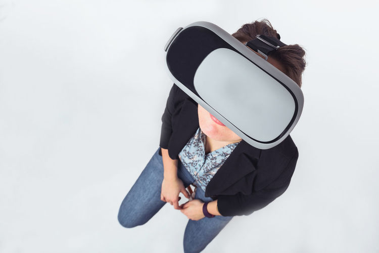 Woman using vr glasses while standing against gray background