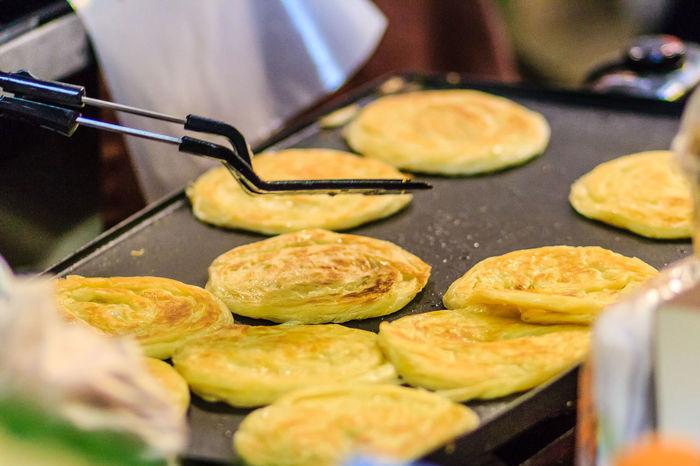 Close up vendor cooking for southern flat bread, mataba, or roti, the popular street food in the night market, Bangkok, Thailand. Kind of Muslim and Indian food Flat Bread Flat Bread Pizza Roti Roti Prata Roti Mataba Roti Telur Roti روتي Close-up Day Dessert Food Food And Drink Freshness Healthy Eating Indoors  Mataba Mataba Roti Matabasiako No People Preparation  Preparing Food Ready-to-eat Roti Canai Roti Canai And Curries Roti Jala Roticanai Selective Focus Serving Tongs Sweet Food Table Temptation Tray