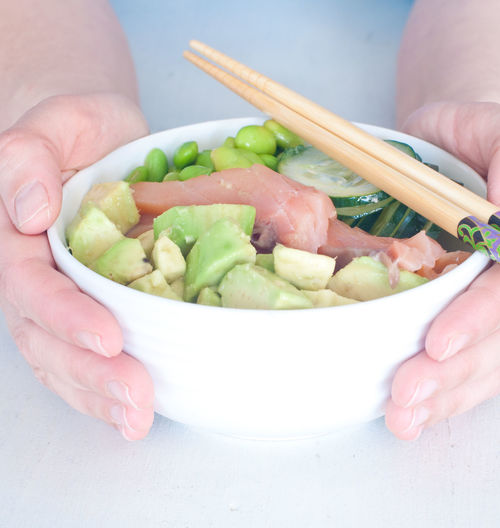 Midsection of person holding salad