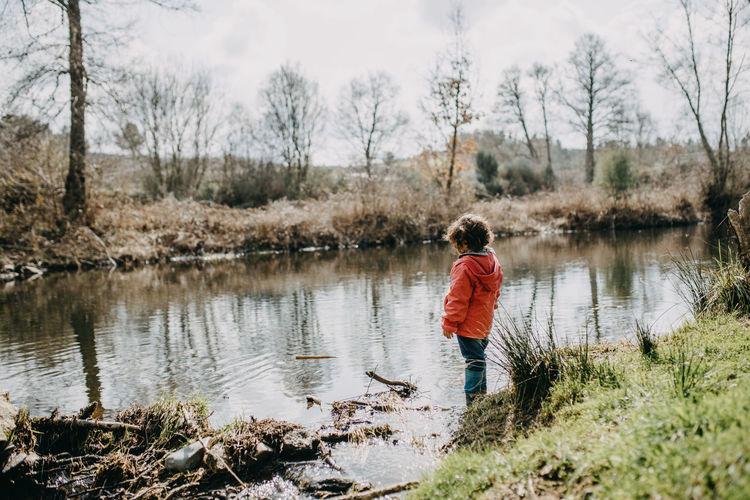 Full length of girl standing by pond