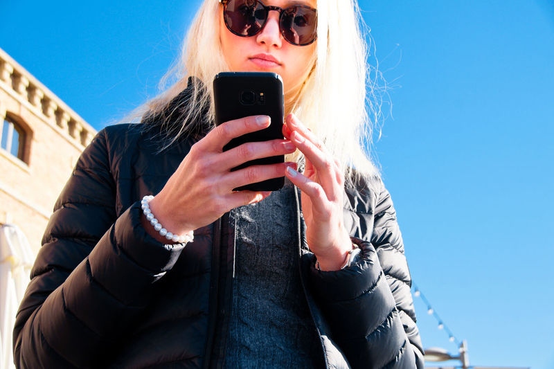 Low angle view of woman using phone against clear sky