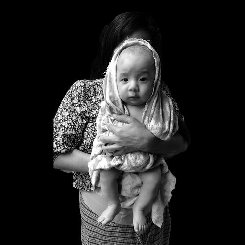 Mother Holding Baby Girls While Standing Against Black Background