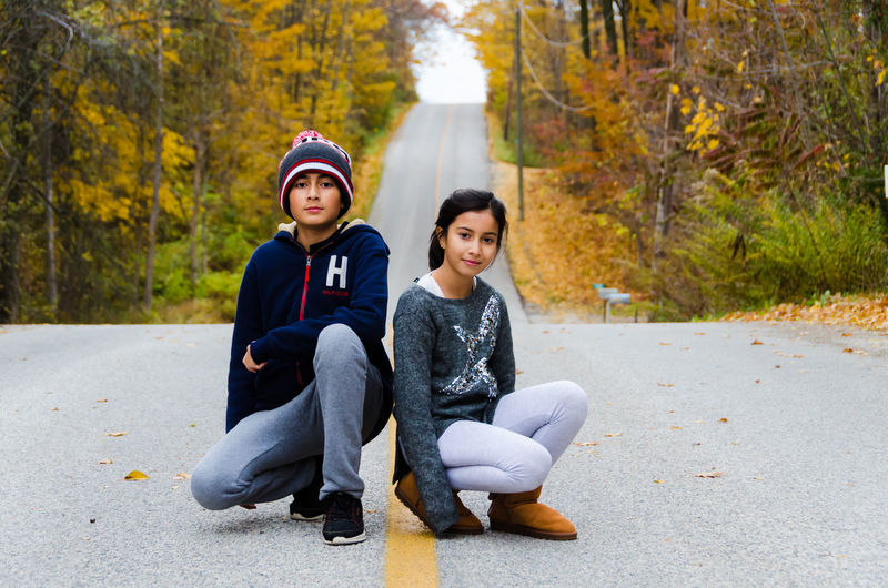 Portrait of smiling siblings crouching on road during autumn