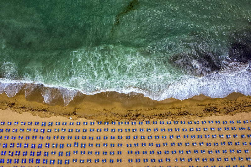 Aerial view of an amazing beach with white umbrellas, lounge chair, and turquoise sea. Tropical sea beach coastline, summer holiday. Aerial View Nature Sea Beach Beautiful Drone  Dronephotography Background Waves Scenics Scenery Umbrella Coast Coastline Dji Colorful Amazing View Top Droneshot