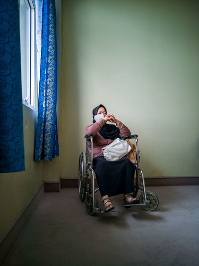Portrait of a senior woman wearing hijab on wheelchair in a hospital.