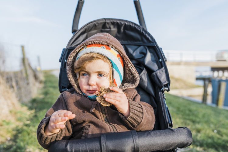 Cute Baby Girl Eating Cookie While Sitting In Stroller