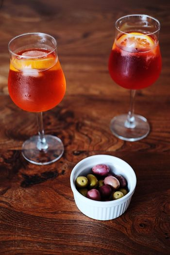 High angle view of olives and aperitif drinks on table