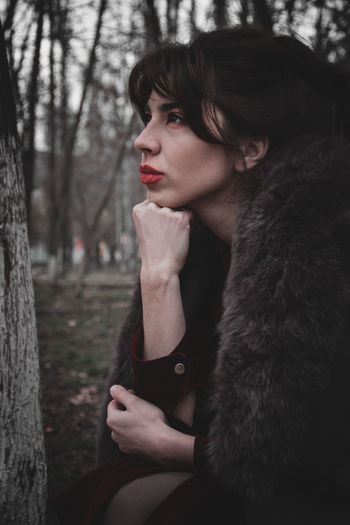 Portrait of woman looking away while sitting on tree