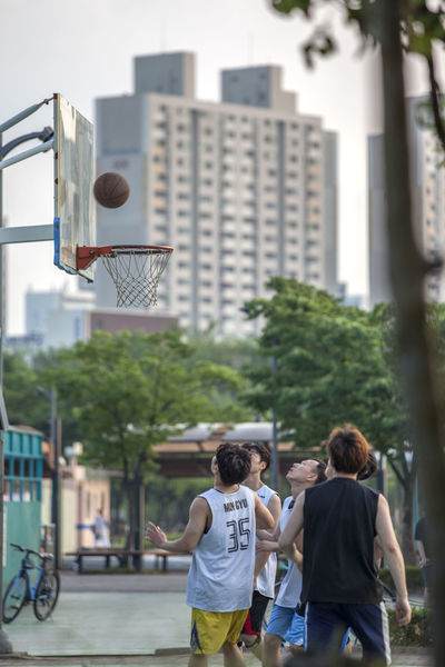 Architecture Athlete Basketball Building Built Structure Casual Clothing City City Life City Street Day Dynamic Focus On Foreground Hover Hovering Leisure Activity Lifestyles Outdoors Players Sky Staring Tree