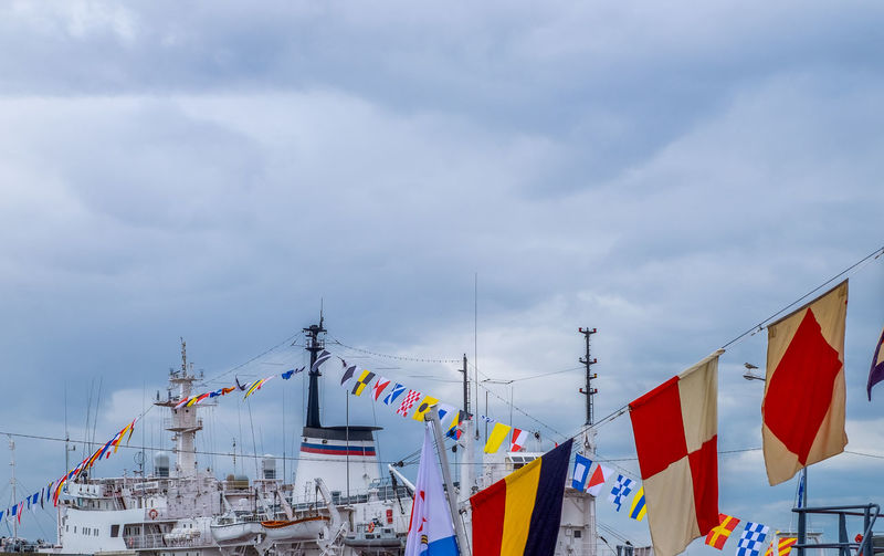 Low angle view of flags on sailboat against sky