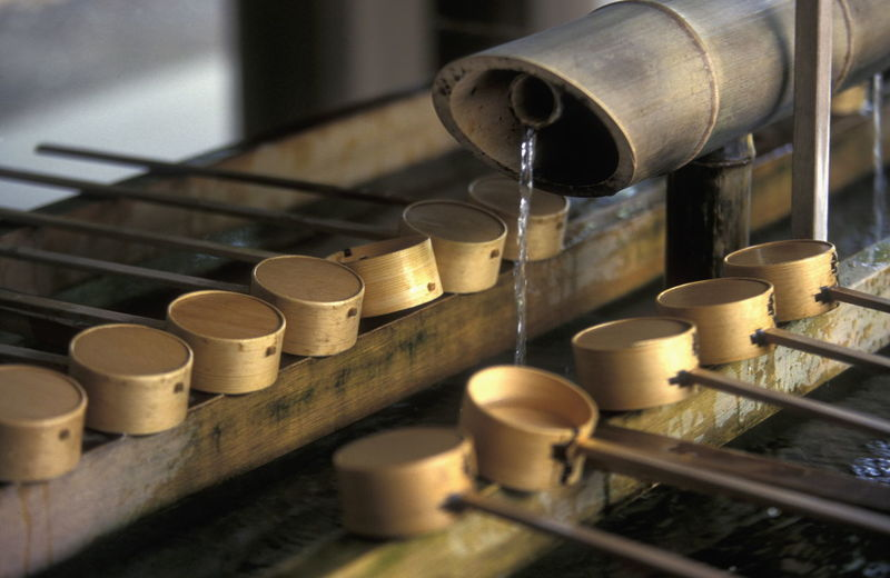 Close-Up Of Ladles On Drinking Fountain