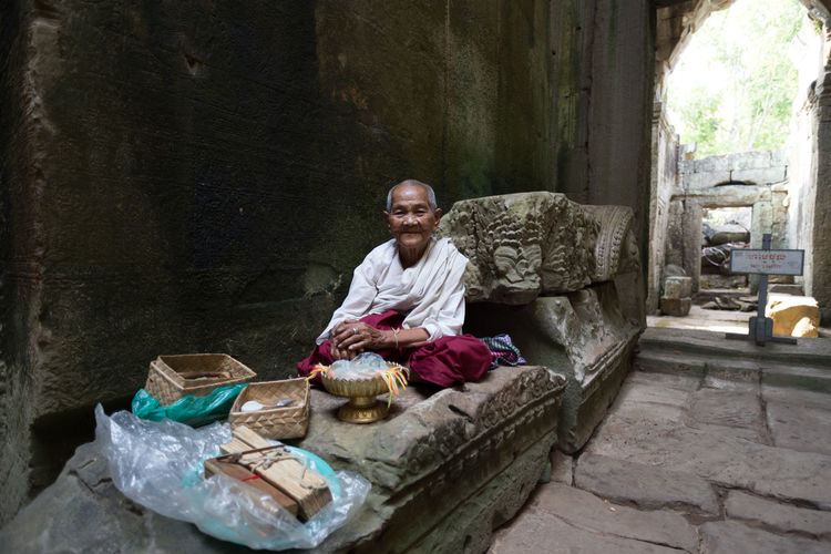 A woman sells prayer in the Angkor temple complex, Cambodia Angkor Buddhism Crosslegged Interaction People Person Portrait Prayers Religion Smile Spiritual Spirituality Temple Traveling Woman