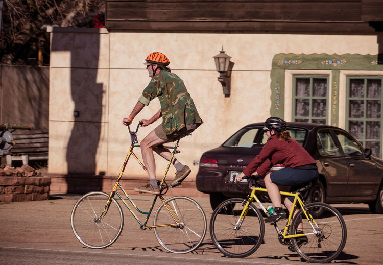 A man rides a custom-made tall bike on the street, accompanied by a woman. Bicycle Celebrate Your Ride Couple Creativity Custom Cycling Funny Homemade Bike Humor Man Quirky Riding Bike Street Tall Bike Woman CyclingUnites