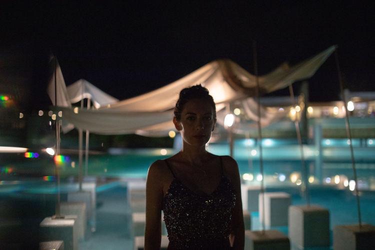 Portrait of woman standing against illuminated restaurant at night