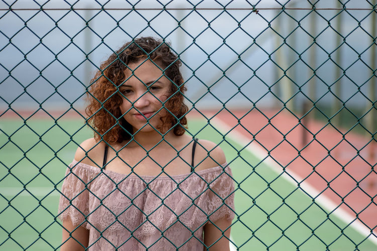Portrait of young woman standing by chainlink fence