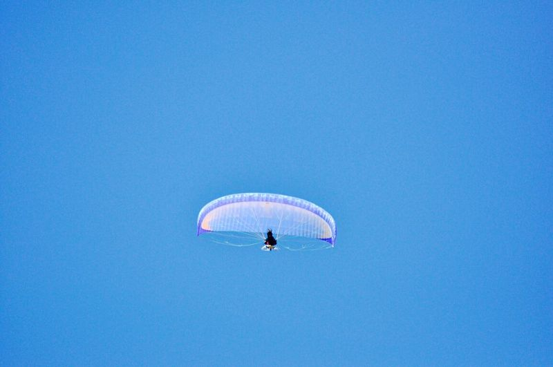 Low Angle View Of Person Flying With Parachute Against Clear Blue Sky