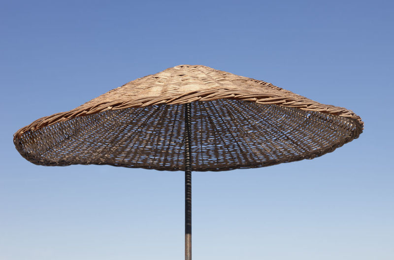 Beach Umbrella against blue Sky Clear Sky Rattan Summer Views Summertime Sunny Vacations Wicker Beach Beach Umbrella Blue Sky Close-up Concept Craft High Section No People Outdoors Parasol Single Object Straw Summer Sunshade Tourism Tropical Umbrella Umbrellas