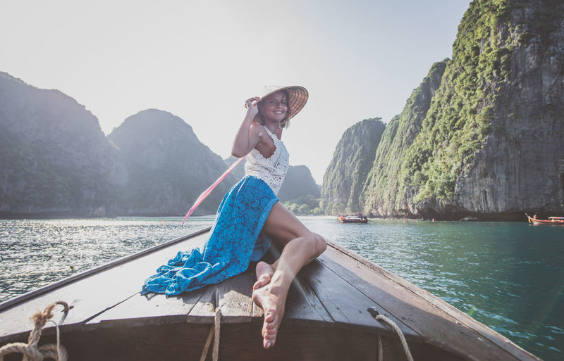 Woman sitting on boat against mountains against sky