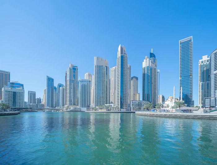 Sea by buildings against clear blue sky