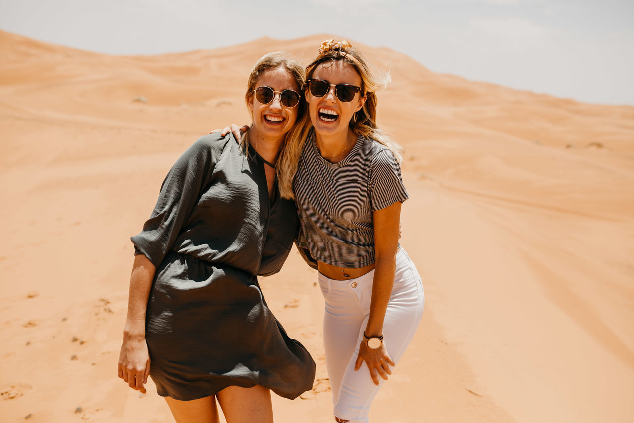 Cheerful friends standing on sand at desert against sky