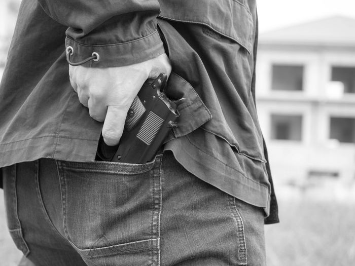 Midsection Of Thief Removing Gun From Back Pocket