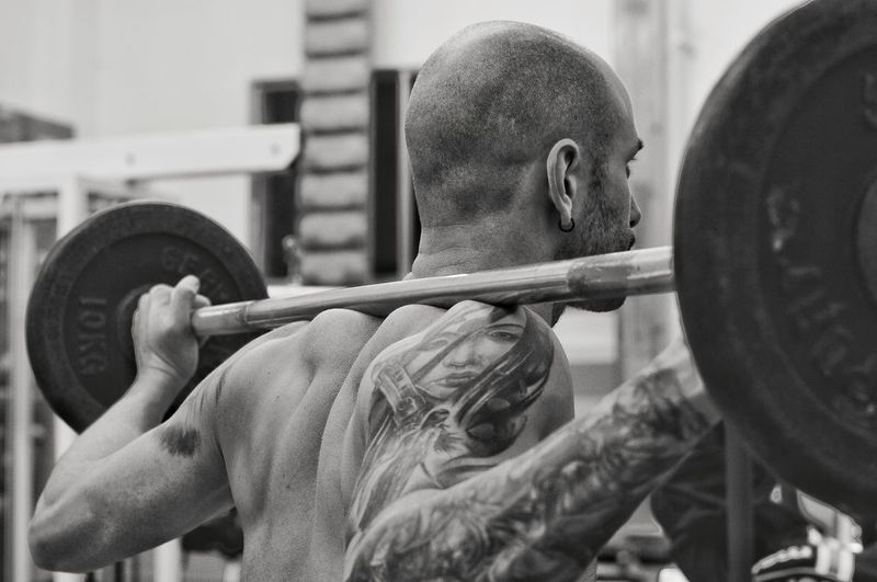 Man Exercising With Barbell In Gym