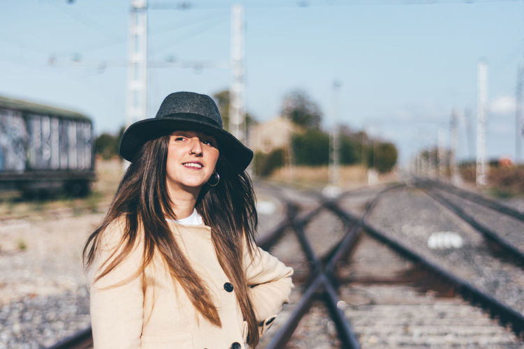 Portrait of smiling young woman standing on railroad track