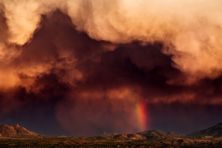 Dramatic stormy sky with rainbow and turbulent, dark clouds over Globe, Arizona. Arizona Dark Ethereal Extreme Monsoon Ominous Storm Weather Awe Beauty In Nature Cloud - Sky Landscape Mountain Nature Outdoors Power In Nature Powerful Rainbow Scenics Sky Stormy Sunset Surreal Thunderstorm Wonder