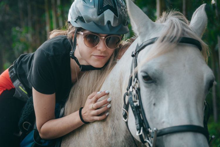 Woman wearing sunglasses and helmet riding horse