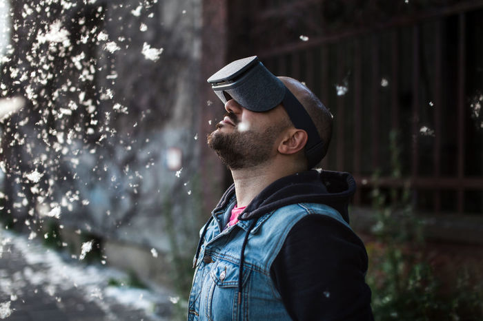 Man wearing VR goggles on a street during summer day while cottonwood fluff is flying around Arms Arms Outstretched Arms Raised Beard Cottonwood Flying Hands Headset Hipster Jeans Man Modern Out Outdoors Technology Virtual Reality Virtual Reality Headset Virtual Reality World Vr Young Adult