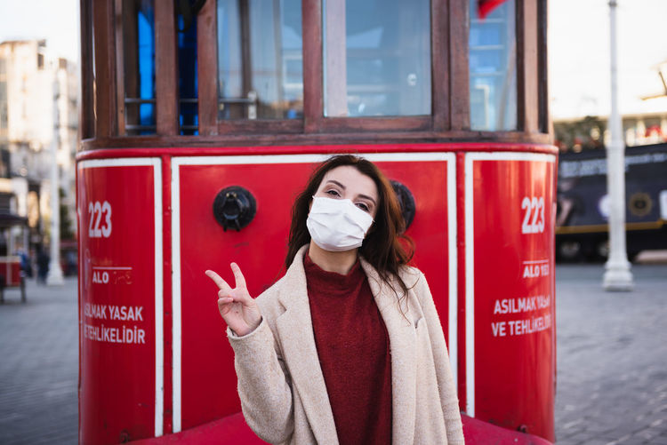 Portrait of woman wearing mask standing against cable car outdoors