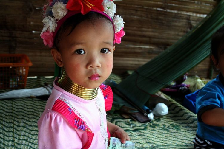 Babygirl Childhood Children Culture Cute Elementary Age Girls Innocence Lifestyles Looking At Camera Nek Person Portrait Rings Sitting Thailand Spotted In Thailand Telling Stories Differently My Favorite Photo This picture shows a little girl who belongs to the padaung tribe. In this tribe woman wear rings around their neck. I think that in this picture we can see the sadness in the eyes of this child. In fact it s not a choice to wear the rings, you have to if you want to stay in the clan. The Portraitist - 2016 EyeEm Awards
