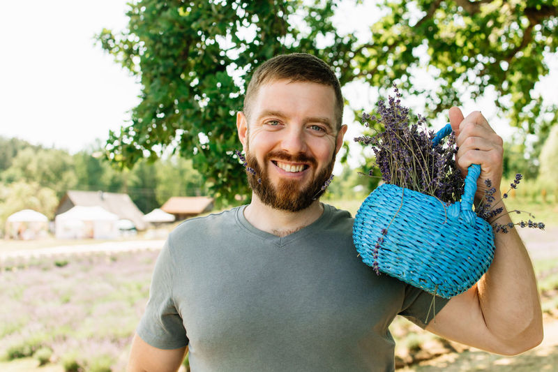 Close up of bearded smiling  man with basket of flowers in lavender field