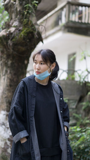 Young woman with flu mask looking away while standing in park